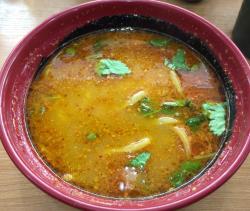 特急レーンデ運ばれてきた直後の担々麺。スープの量が多く、麺が隠れてしまっている。三つ葉や胡麻もPR写真ほどのインパクトはないが、味はばっちり。